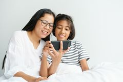Asian mother and daughter playing game with phone together on the bed. Women and girl so happy and fun in bedroom royalty free stock image