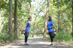 Asian mother and daughter warm up before running at the park royalty free stock images