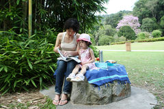 Asian mother and daugther reading at garden. Mother teach her daughter reading a book at garden Stock Image