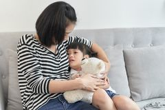 Asian mother embrace little preschool frustrated kid sitting on couch together at home.  stock images