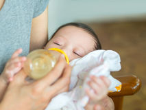 Asian mother feeding bottle her baby while baby sleeping and hol Royalty Free Stock Images