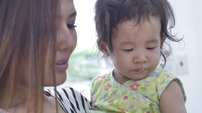 Asian mother feeding food for her daughter at home with smile face, Happy asian family concept. Asian mother is feeding food for her daughter at home with smile stock video footage