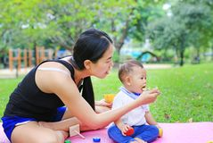 Asian mother feeding food for infant baby boy sitting on pink mattress mat in the garden.  stock image
