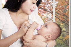 Asian mother feeding her baby girl Royalty Free Stock Photo