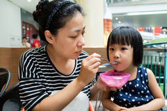Asian Mother Feeding Her Daughter Stock Images