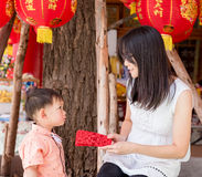 Asian mother give a red envelope or Ang-pow to son stock photo