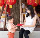 Asian mother give a red envelope or Ang-pow to son. As a Chinese new year gift stock photo