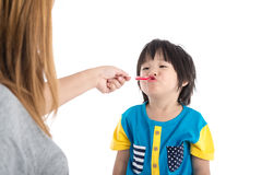 Asian Mother giving her son syrup Stock Photo
