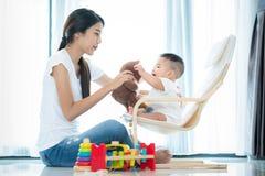 Asian mother and har baby play teddy bear togather stock photos