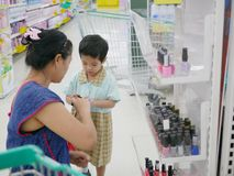 Asian mother helping her little daughter selecting nail polish stock photography