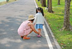 Asian mother helping her little daughter to put shoes on the road outdoor stock image