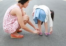 Asian mother helping her little daughter to put shoes on the road outdoor royalty free stock photos