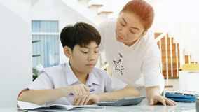 Asian mother helping her son doing homework on white table royalty free stock photo