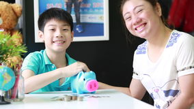 Asian Mother helping son to save money in piggy bank stock video footage