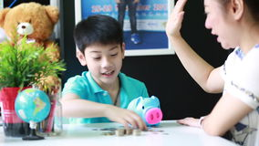 Asian Mother helping son to save money in piggy bank stock footage