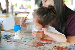 Asian Mother and her daughter having fun to paint on stucco doll royalty free stock photo