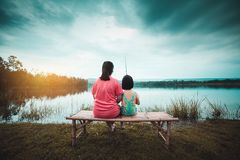 Asian mother and her daughter sit on the banks of a tranquil evening lagoon stock photography