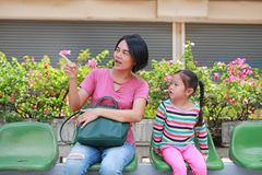 Asian mother and her daughter sitting at bus station. Mom and child girl passenger waiting for public transport royalty free stock images