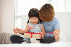 Child daughter unwrapping gift box with her mom. Asian mother and her daughter unwrapping gift box. Mum and girl smiling and hugging on bed in their bedroom royalty free stock photography