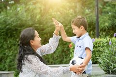 Asian mother high-fiving son with ball. Side view of adult Asian women smiling and giving high five to sweet boy with football ball while spending time in park stock image