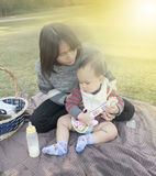 Asian Mother hold baby when family picnic in the park Royalty Free Stock Image