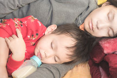 Asian mother holding baby in arm while baby drinking milk from bottle stock photography