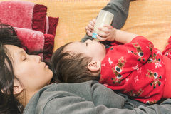 Asian mother holding baby in arm while sleeping Stock Image