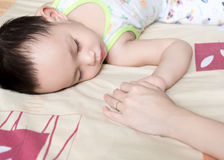 Asian mother holding baby hand while sleeping stock images