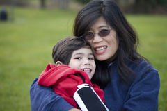 Asian mother holding disabled son at park. Beautiful asian mother holding her disabled son at park Royalty Free Stock Photos