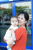 Asian mother holding her baby and smiling Stock Photos