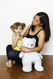 Asian mother holding her 3-year-old daughter. Precious three-year-old girl sits on her mothers lap, cuddling her blue teddy bear and looks at the camera Royalty Free Stock Photos