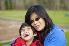 Asian mother holding son at park Royalty Free Stock Images