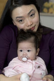 Asian Mother holds her daughter. Asian mother holds her infant daughter play in their home. Great family shot stock image