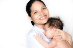 Asian mother holds her newborn baby. An Asian mother lovingly holds her 1 month old mixed race baby boy Royalty Free Stock Photos