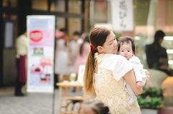 Asian mother hugging her baby outdoors Royalty Free Stock Images