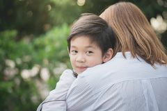 Asian mother hugging with her son in the park. Happy asian mother hugging with her son in the park royalty free stock photos