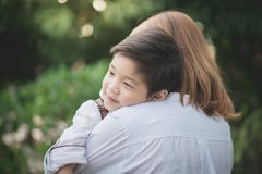 Asian mother hugging with her son in the park. Happy asian mother hugging with her son in the park stock image