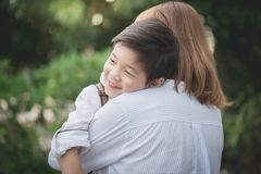 Asian mother hugging with her son in the park. Happy asian mother hugging with her son in the park Stock Photography