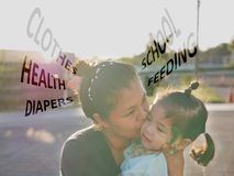Asian mother hugging and kissing her daughter, while worrying about her daughter`s clothes, health, diapers, feeding, and school stock photo