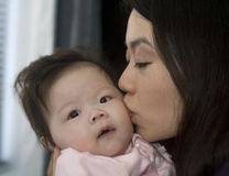 Asian Mother Kisses her daughter. An asian mother kisses her baby girl in her home. Has love written all over it royalty free stock photography