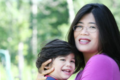 Asian mother lovingly holding her son. Asian mother lovingly holding her disabled son outdoors in summer. Child is biracial, asian caucasian background Royalty Free Stock Photo