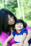 Asian mother lovingly holding her son. Asian mother lovingly holding her disabled son outdoors in summer. Child is biracial, asian caucasian background Royalty Free Stock Image