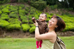 Asian mother playing with her 7 month old baby girl. In a tea plantation in Malaysia Stock Image