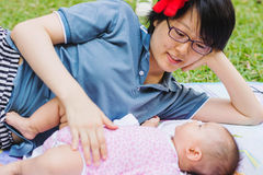 Asian mother playing and taking care of  baby at park Royalty Free Stock Photo