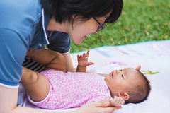 Asian mother playing and taking care of  baby at park Royalty Free Stock Photography