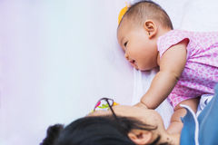 Asian mother playing and taking care of  baby at park Stock Photo