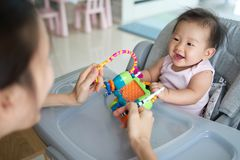 Asian mother playing toy with her baby sitting on the dinning chair at home. They are enjoy playing together with happiness. stock photos