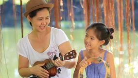 Asian mother playing ukulele for her daughter. In park stock footage