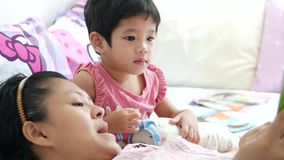 Asian mother reading a bedtime story to her little baby girl stock footage