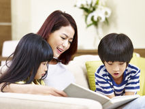 Asian mother reading book with two children. Asian mother sitting on couch at home reading book with son and daughter Royalty Free Stock Image